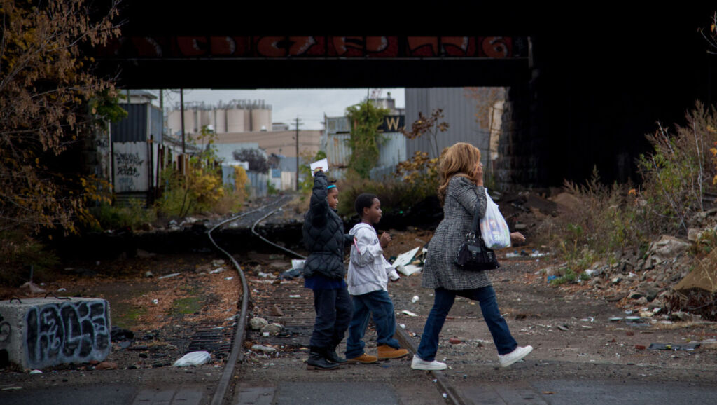 A Black woman and two black children cross railway tracks in Newark. There is litter and graffiti in area.