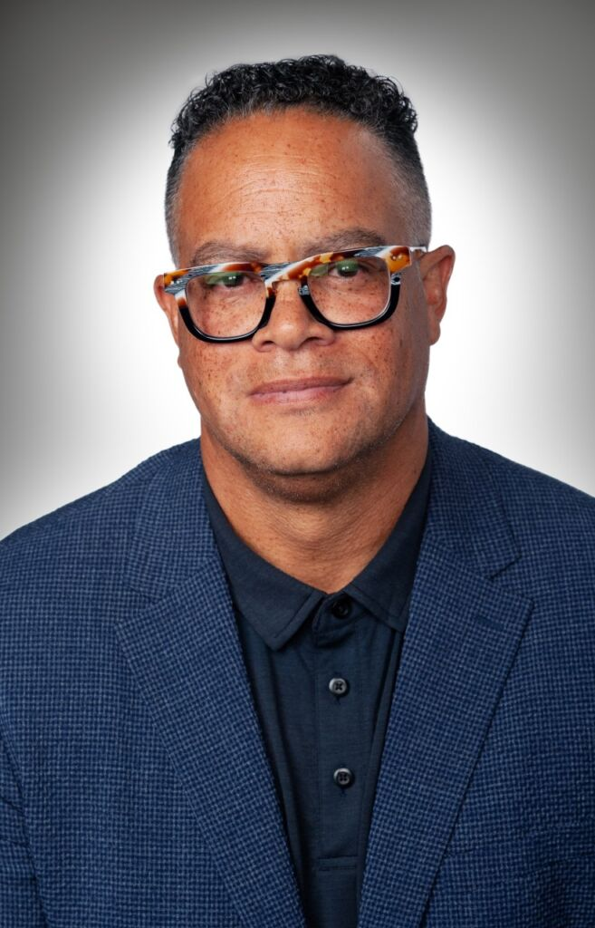 Portrait of light-skinned Black man with freckles and dark blue checked pattern jacket and buttoned up dark shirt. He has two-toned eyeglasses: upper part is multicolored, bottom is solid dark color